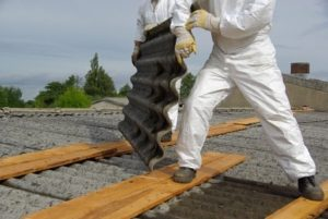 worker removing asbestos roofing